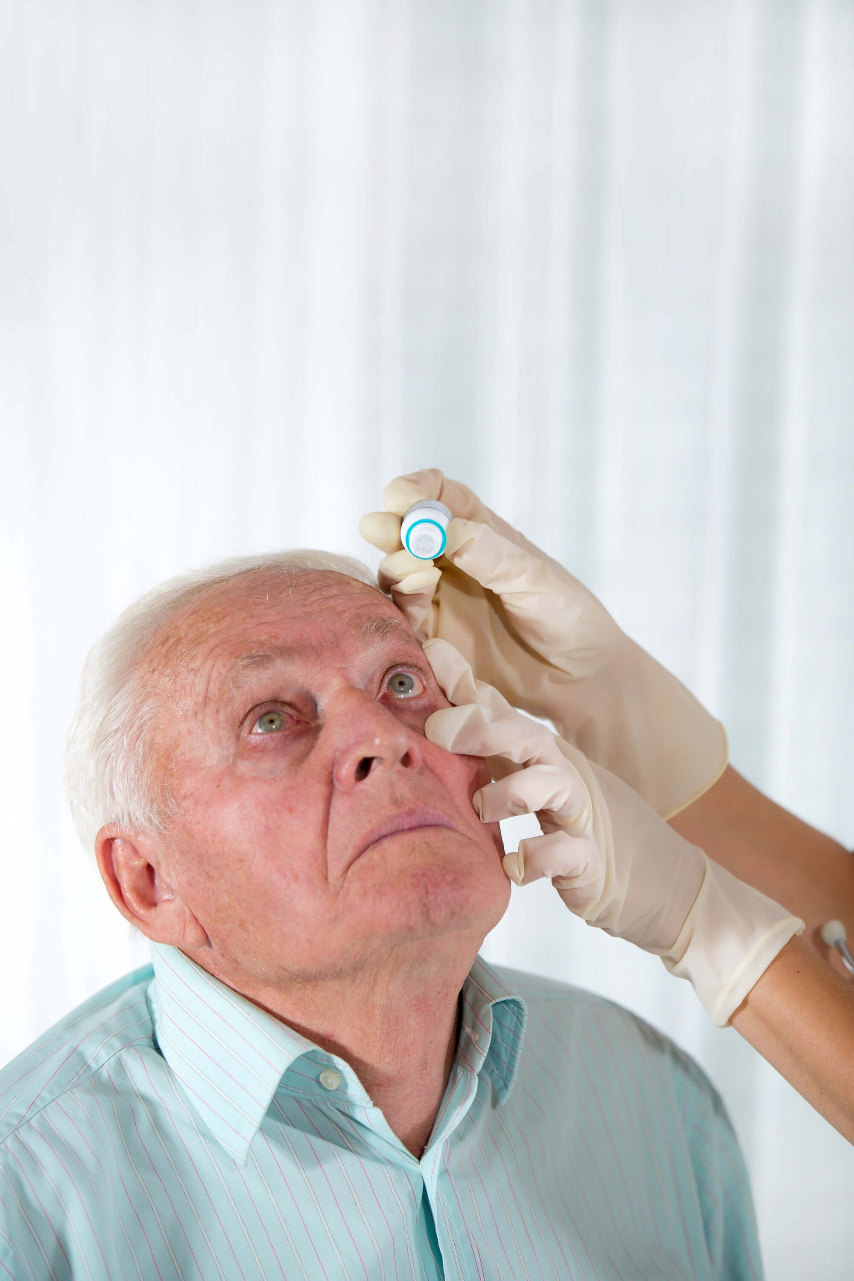 Elderly patient receiving eye drops from eye doctor